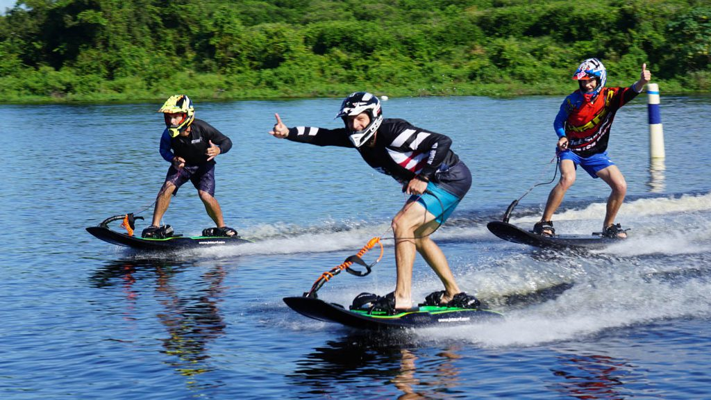 Three people riding the waves in the lake using Jet Surf.
