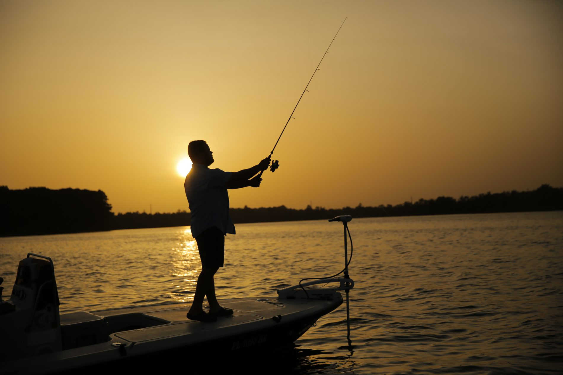 Man standing on deck of bass boat fishing in the middle of a lake as the sun is setting