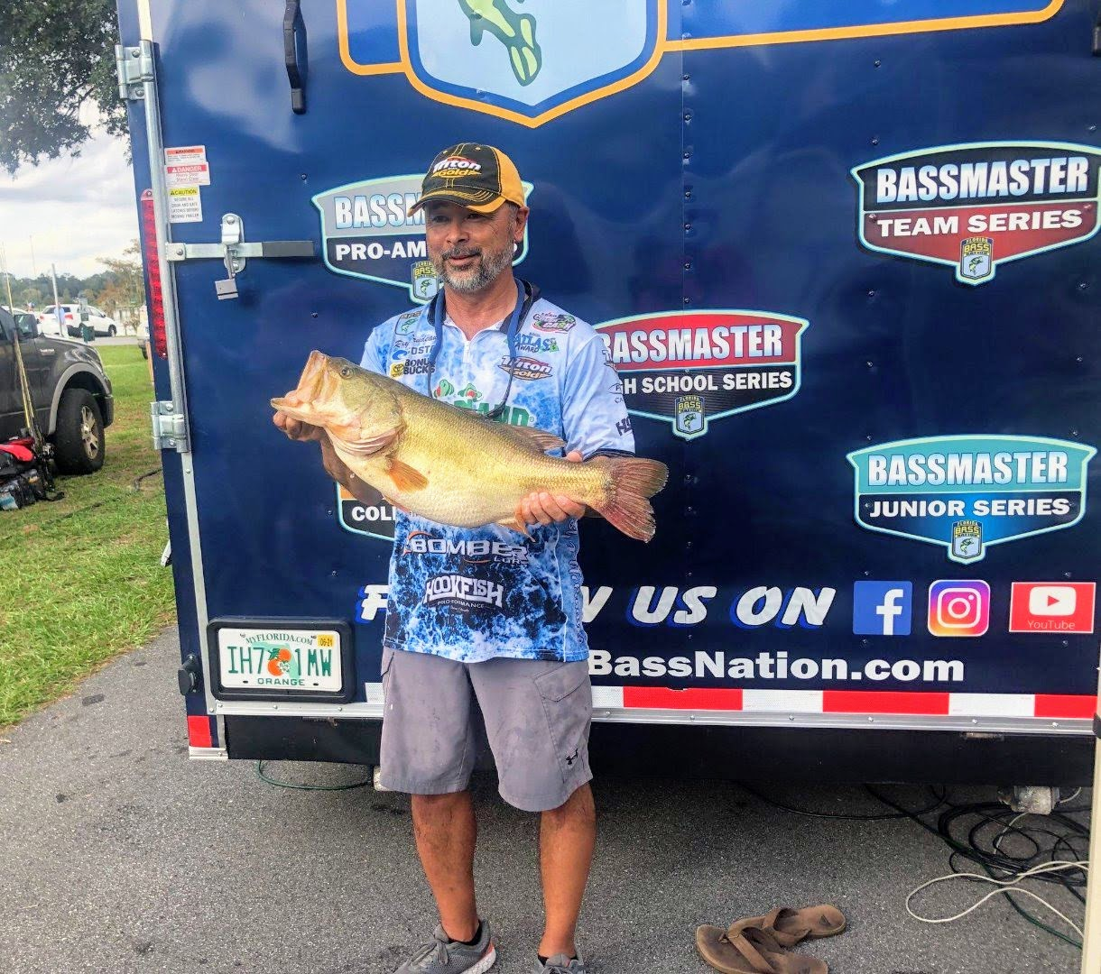 Man standing in front of Bassmaster trailer holding a largemouth bass
