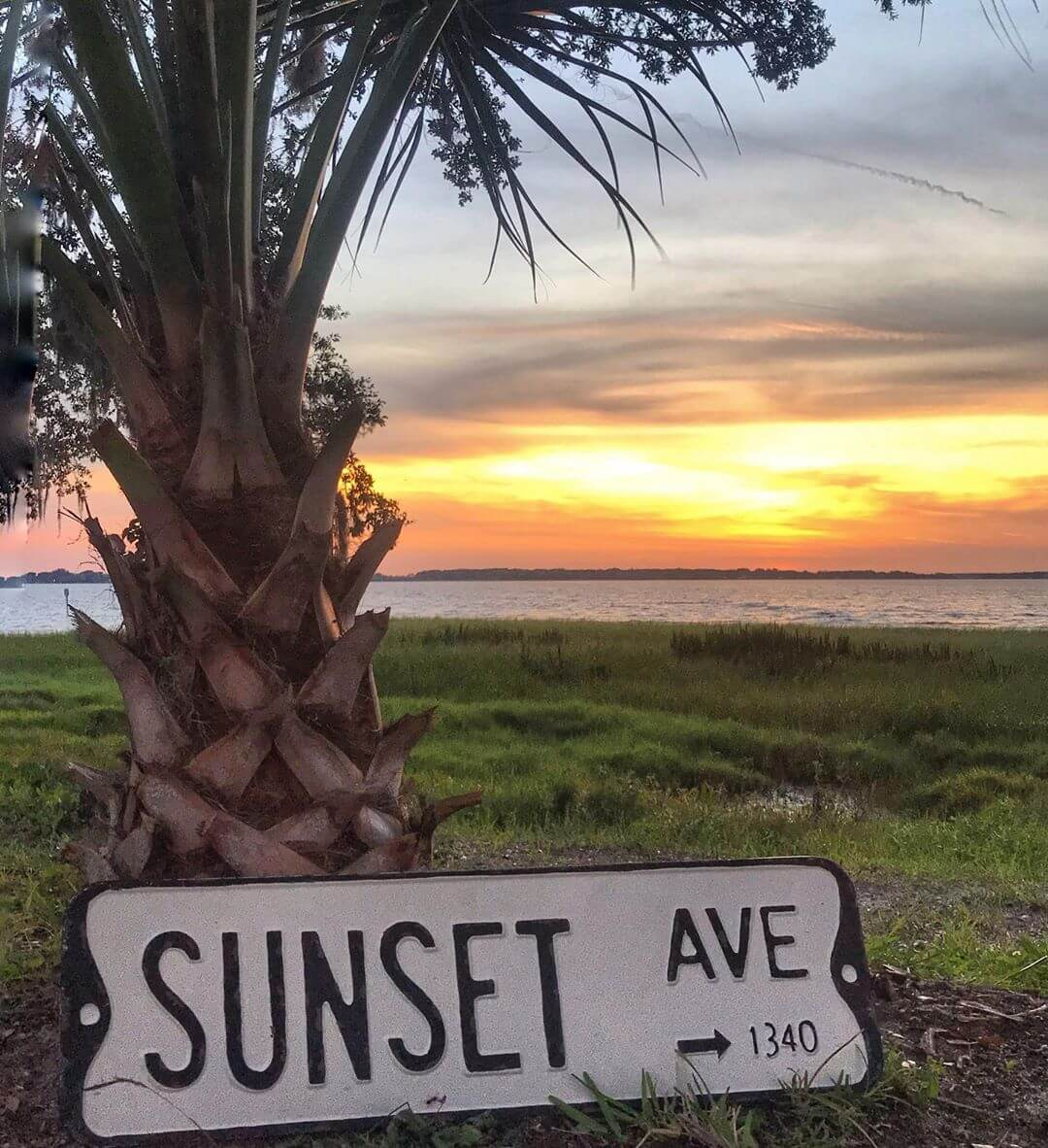 """""""Sunset"""" sign leaning on palm tree with sunset and lake in background"""