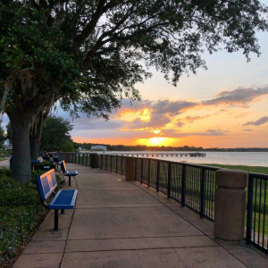 Paved sidewalk with railing and benches along the waterfront of a lake with a pier located in the distance at sunset.