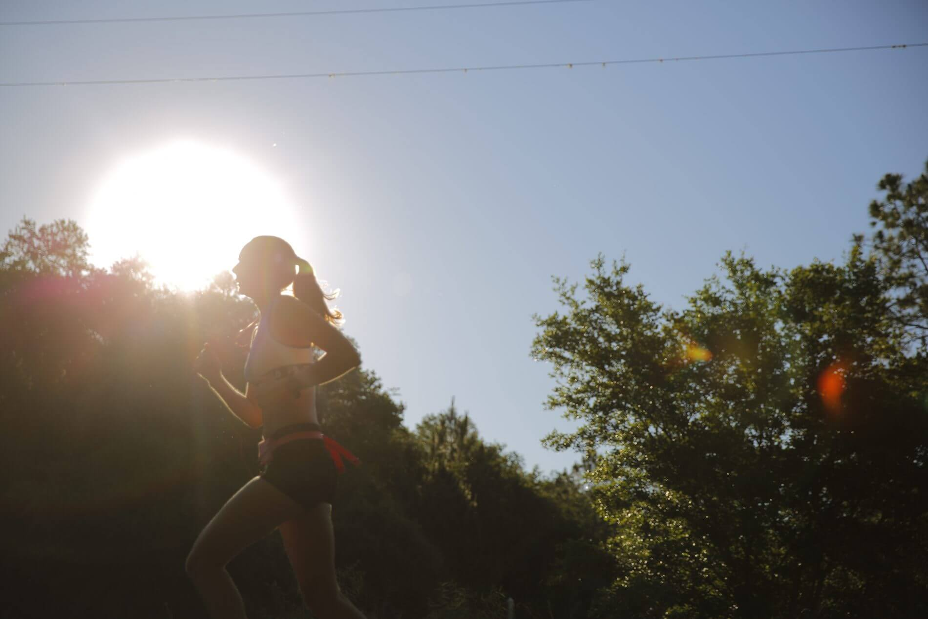 Girl running by herself on a trail with sun and trees in background