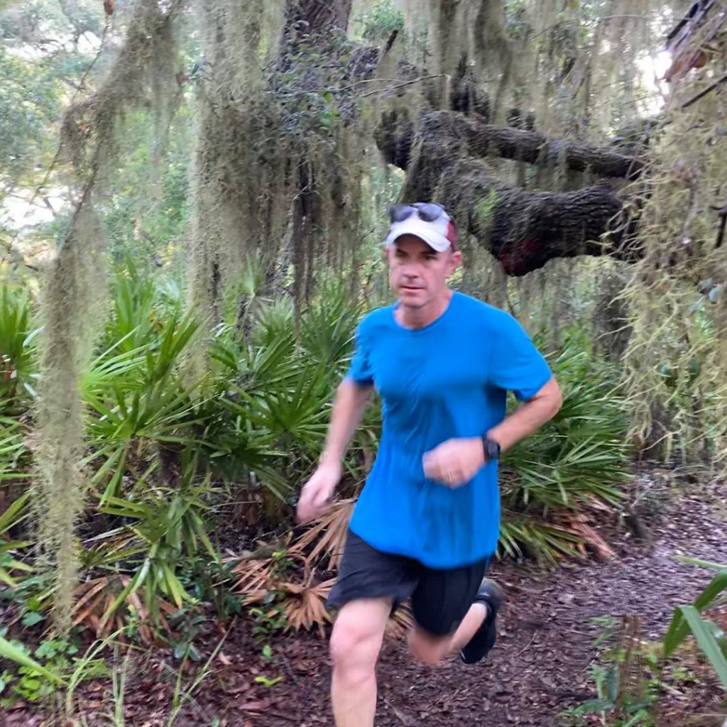 Man dressed in athletic wear running on a dirt trail with a natural surrounding with spanish moss hanging from oak trees behind him.