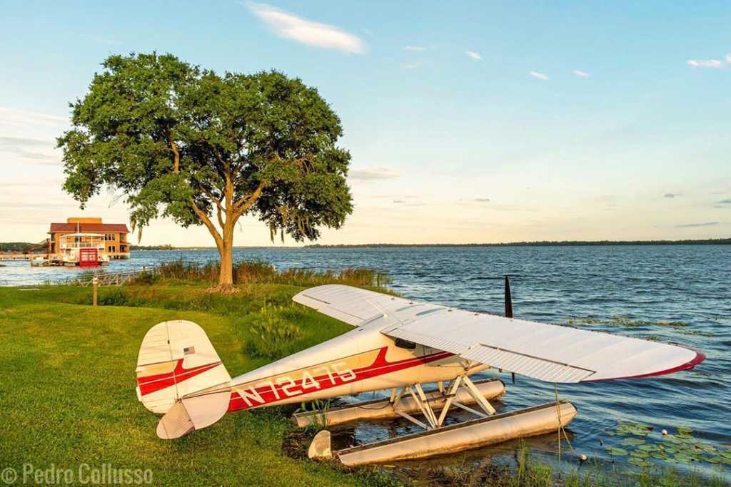 Seaplane parked on the bank of a lake with a building in the background.