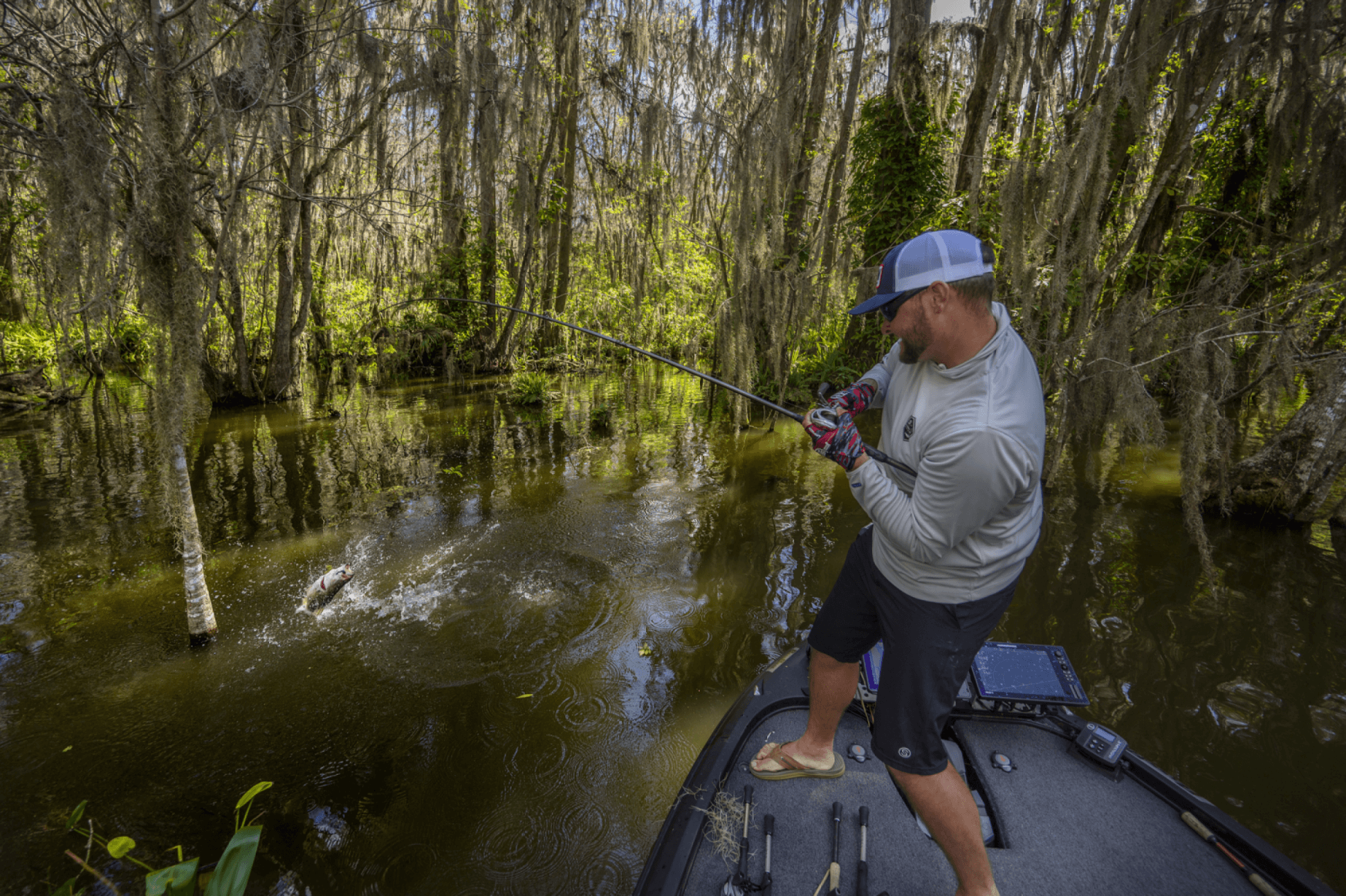 man fishing in a canal catching a largemouth bass