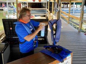 A CatBoat tour staff member sanitizes life jackets.