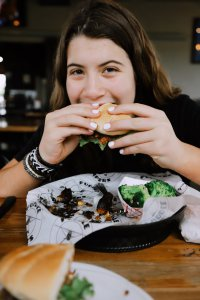 A girl enjoys a meal at a restaurant.