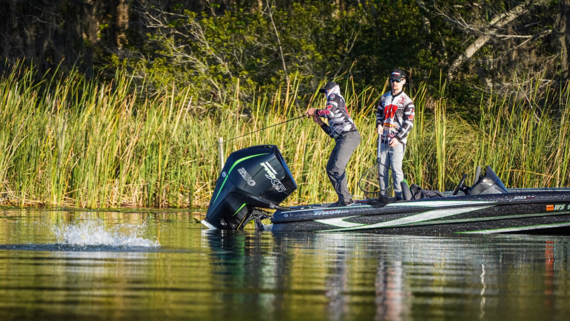 two collegiate anglers standing on the back of a bass boat fighting to reel in a largemouth bass during a tournament