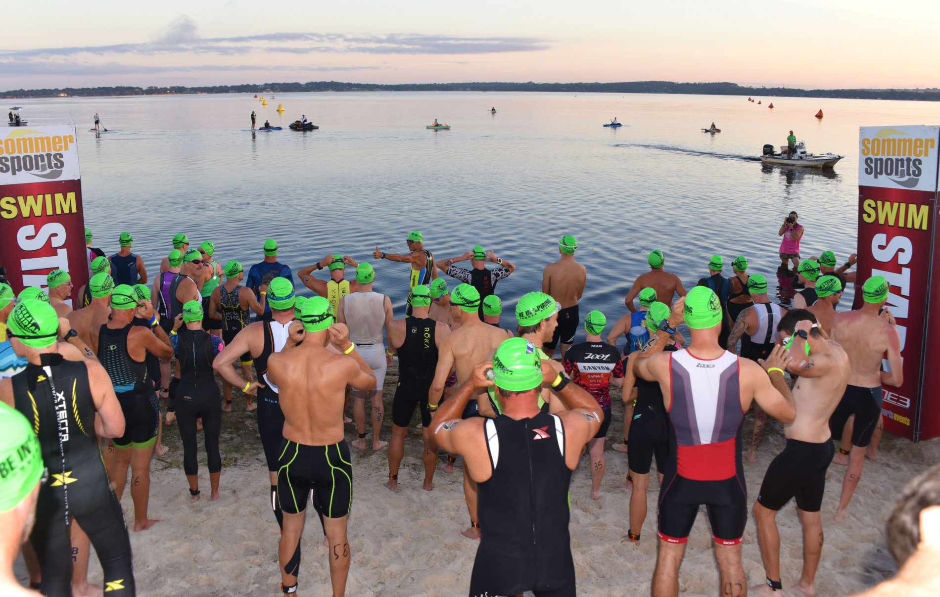 Athletes at start line of a triathlon swim portion of event getting ready to enter a lake.