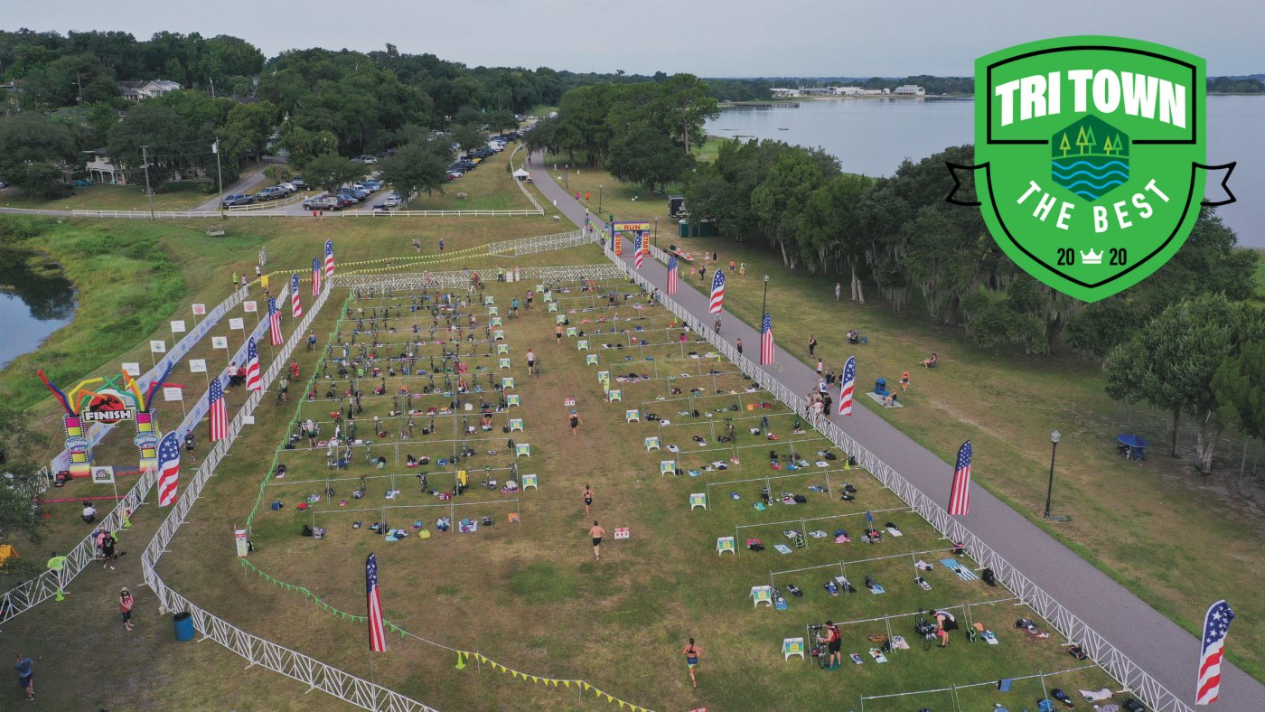 Arial image of an open grass park with rows of bicycles and racks lined up for a triathlon event, a trail runs along a lake.