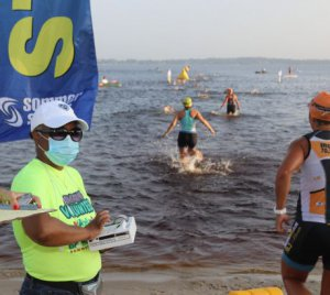 Person in mask standing on shore of a lake marking times as athletes enter water to start triathlon