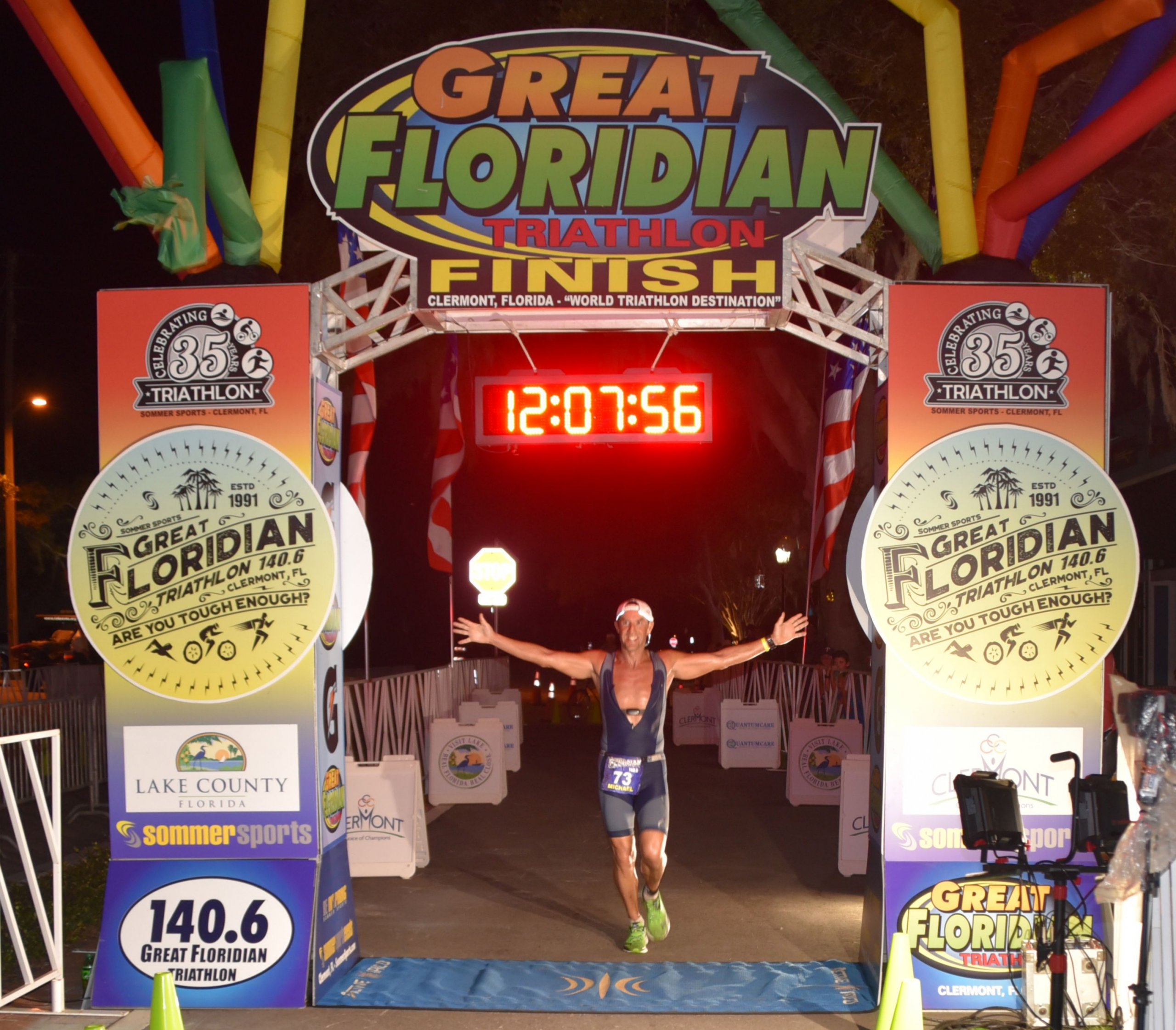 Winning triathlete crossing the fishing line of the great floridian triathlon, time says 12:07:56