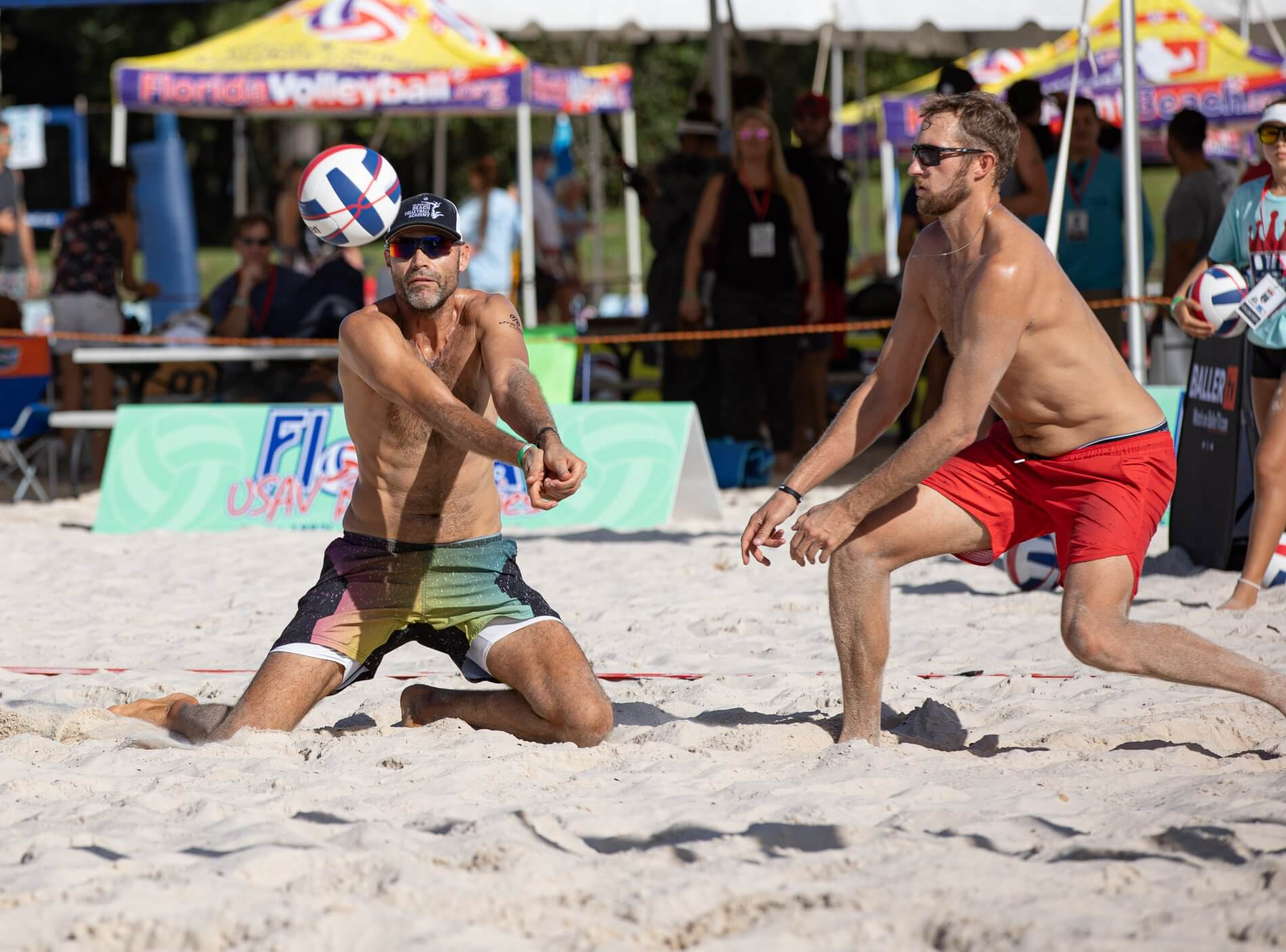 two professional beach volleyball players go for a ball