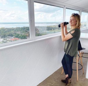 A woman holds binoculars and looks out at the top of the Florida Citrus Tower in Clermont, FL.