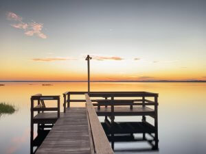 Photo of a pier on a lake at sunrise.