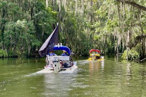 Two cat boats float into the Dora Canal.