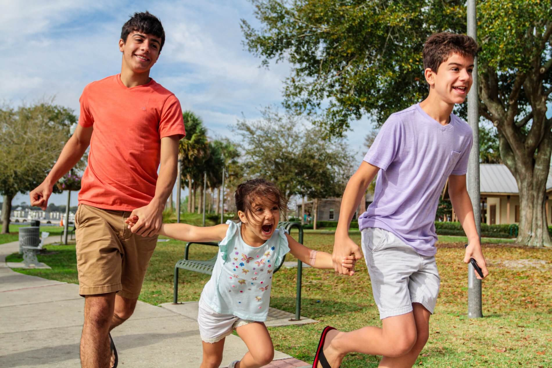 Three siblings run together in a park.