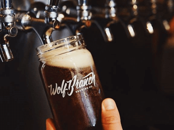 Close-up photo of dark beer from a tap being poured into a glass.