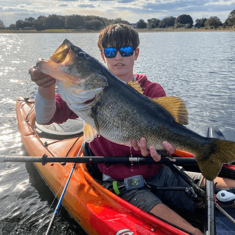 close up of a young man wearing sunglasses and sitting in a kayak in the middle of a lake. he is holding a largemouth bass horizontally.