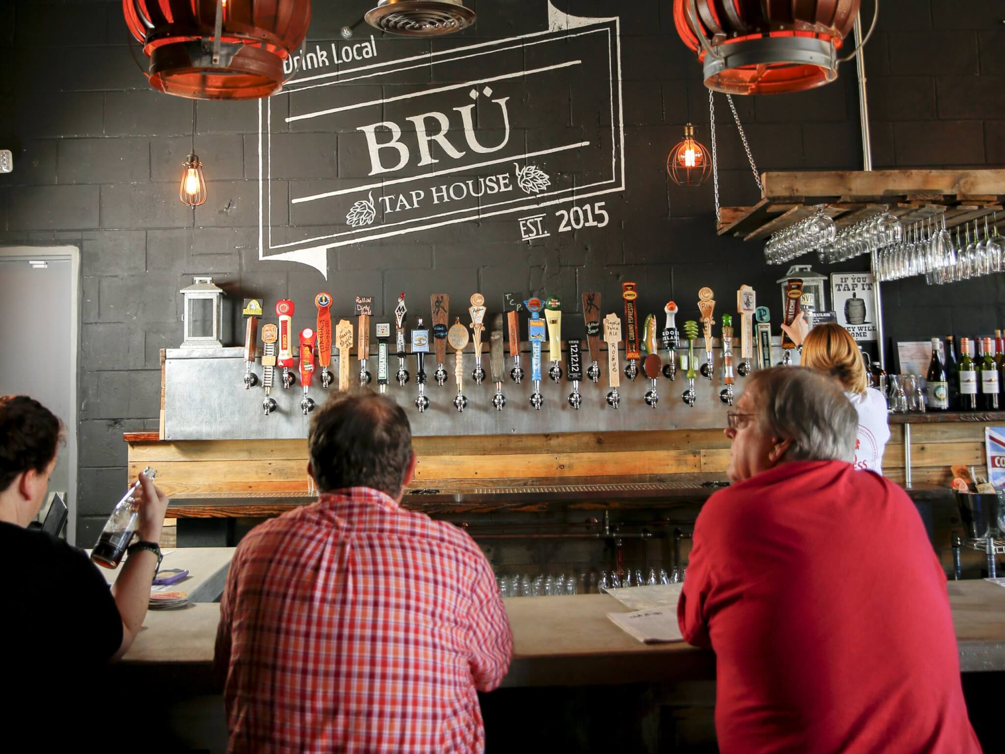 Interior, Bru Tap House, Tavares. Three people are sitting at the bar.