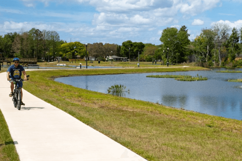 Tavares Ecological Park. A person rides a bike on the sidewalk beside a pond.