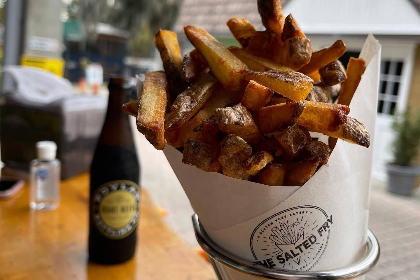 Photo of fries wrapped in a paper container sitting on a table.