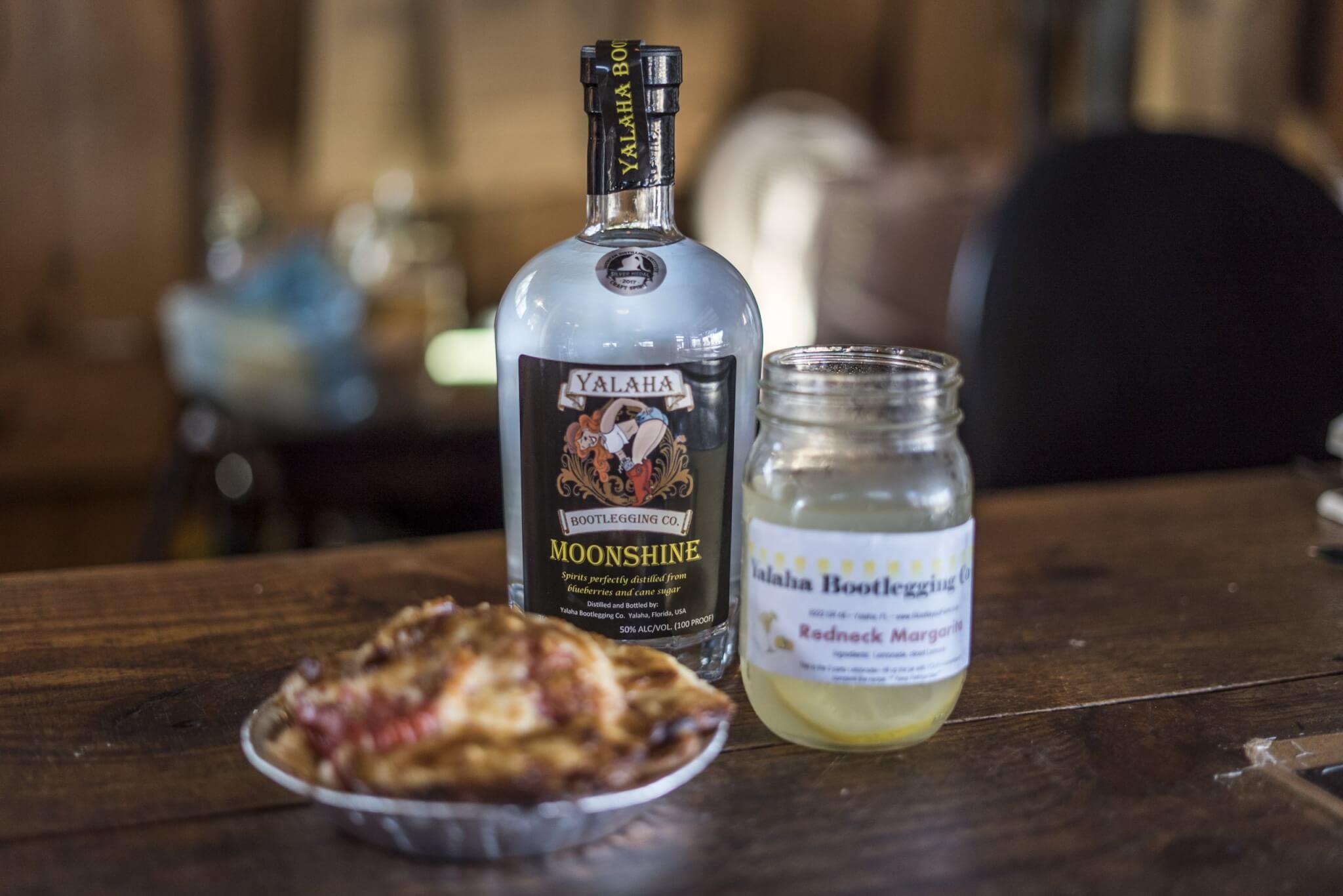 Photo of moonshine bottle and mason jar glass beside a baked pie from the Yalaha Bakery.