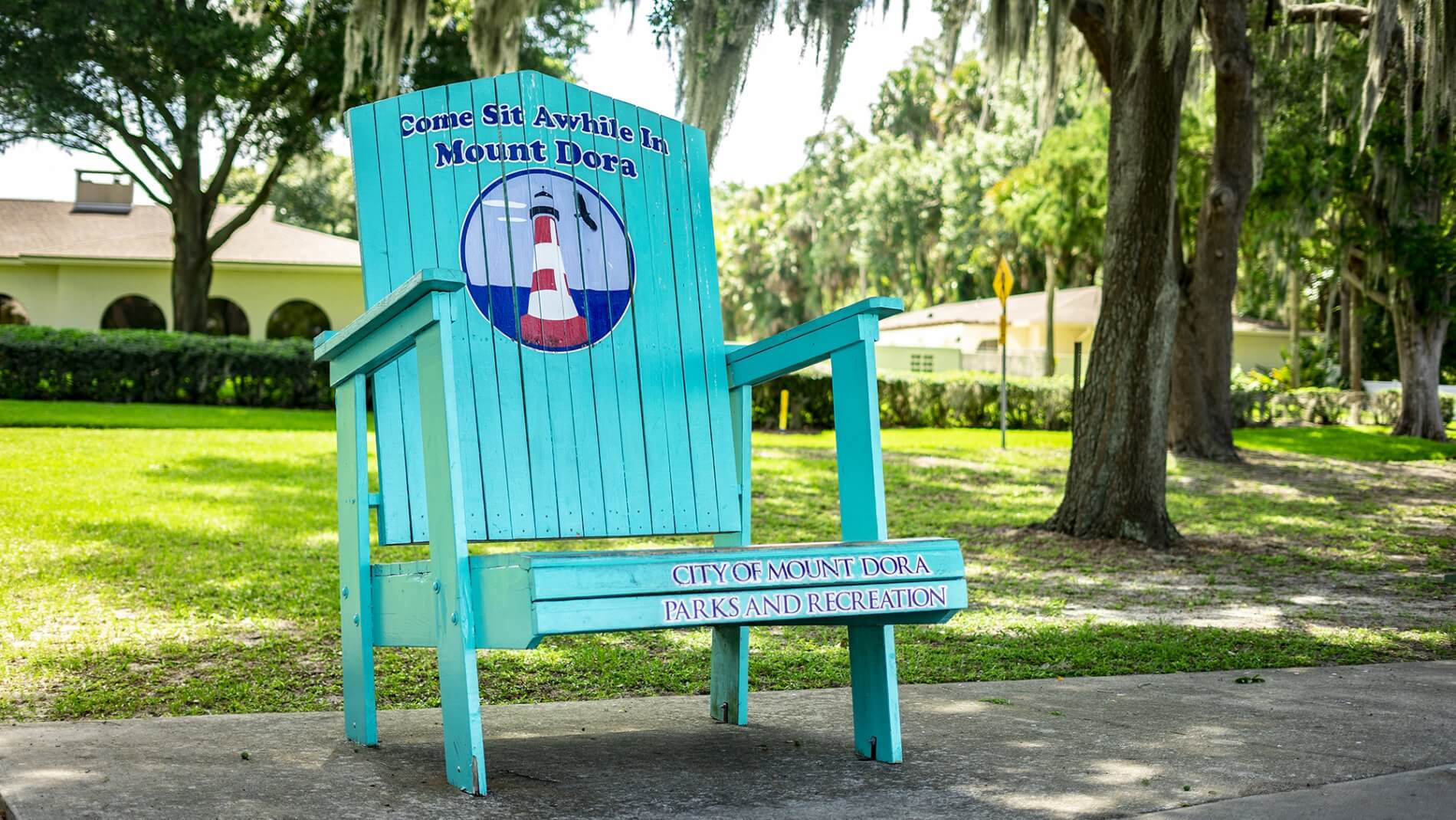 "Photo of a big wooden chair that reads: ""Come sit awhile in Mount Dora."""