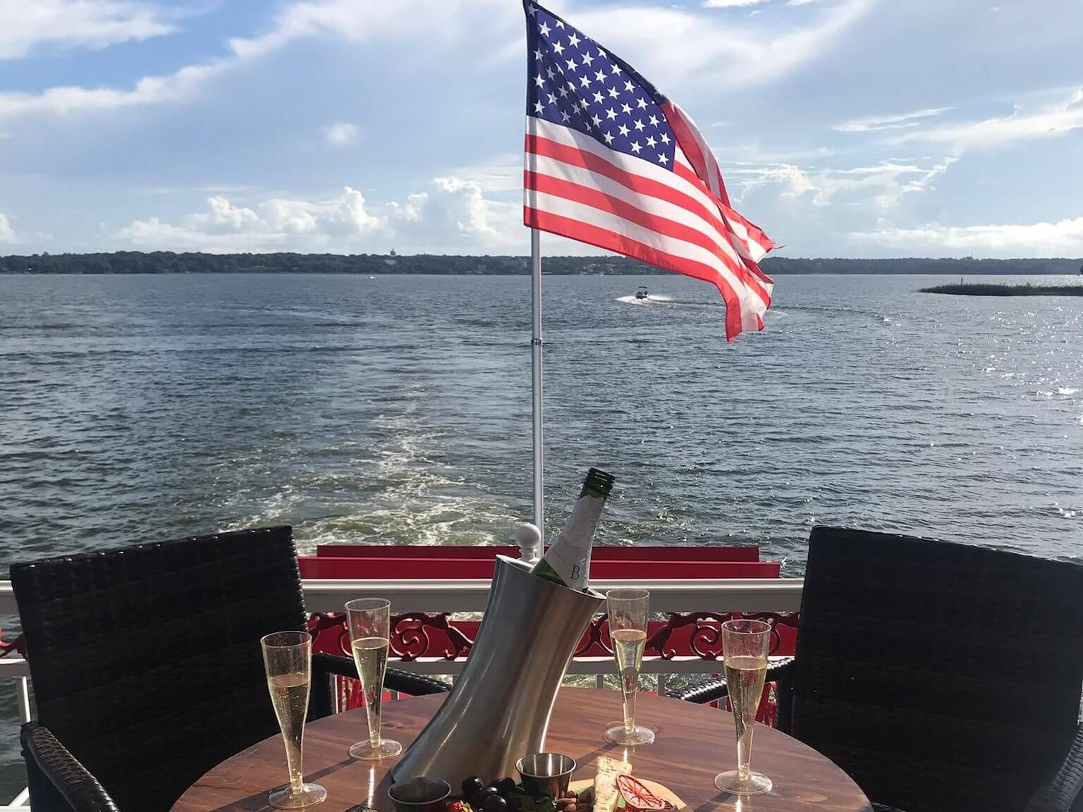 Photo of a table set with 4 glasses of champagne on the upper deck of the Dora Queen paddlewheel boat in the back of the boat. The American flag is seen flying on the boat.