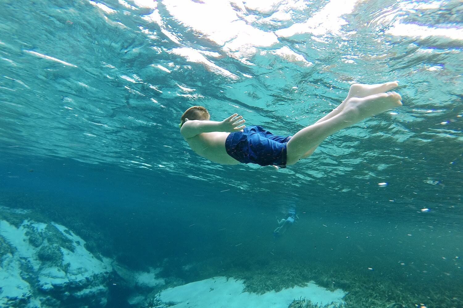 A boy takes a dive into the clear waters of Alexander Springs.