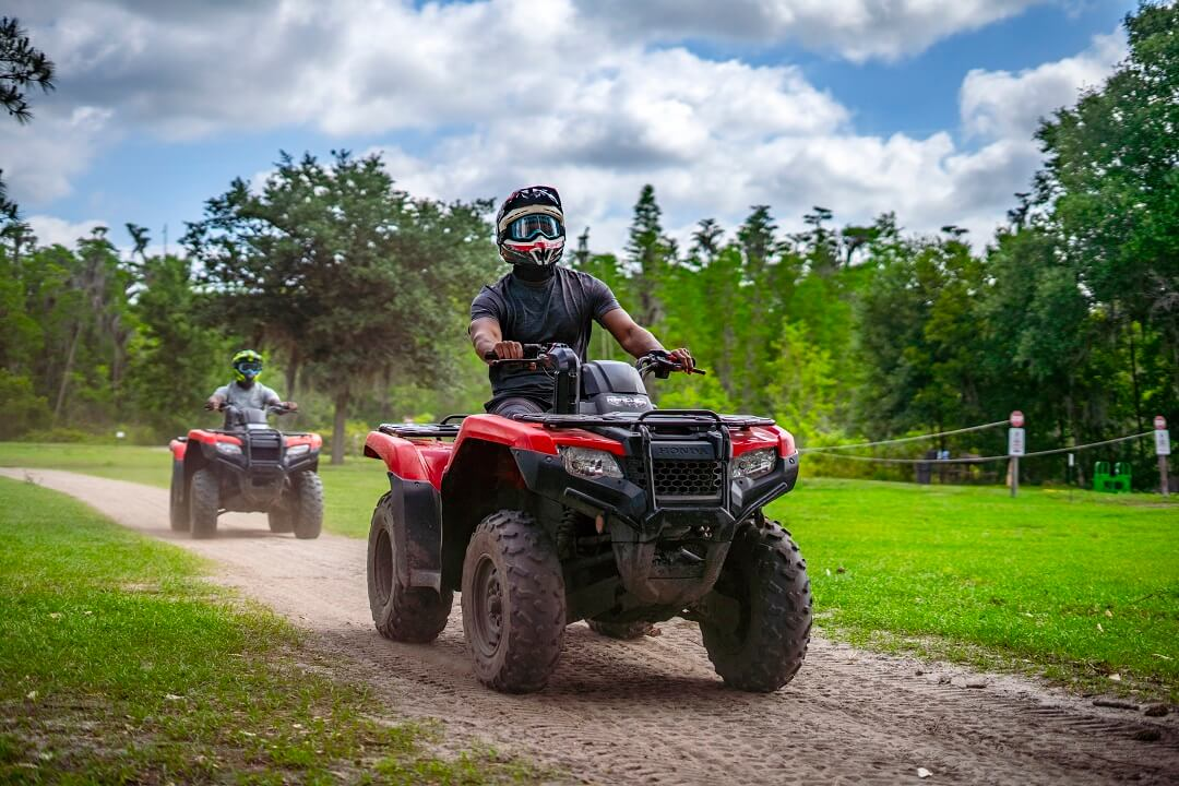 Two people drive ATVs on a dirt road.