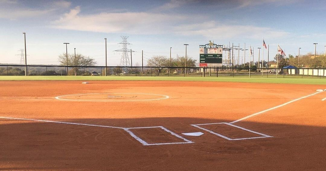 field level view of an empty fastpitch softball field from behind home plate.