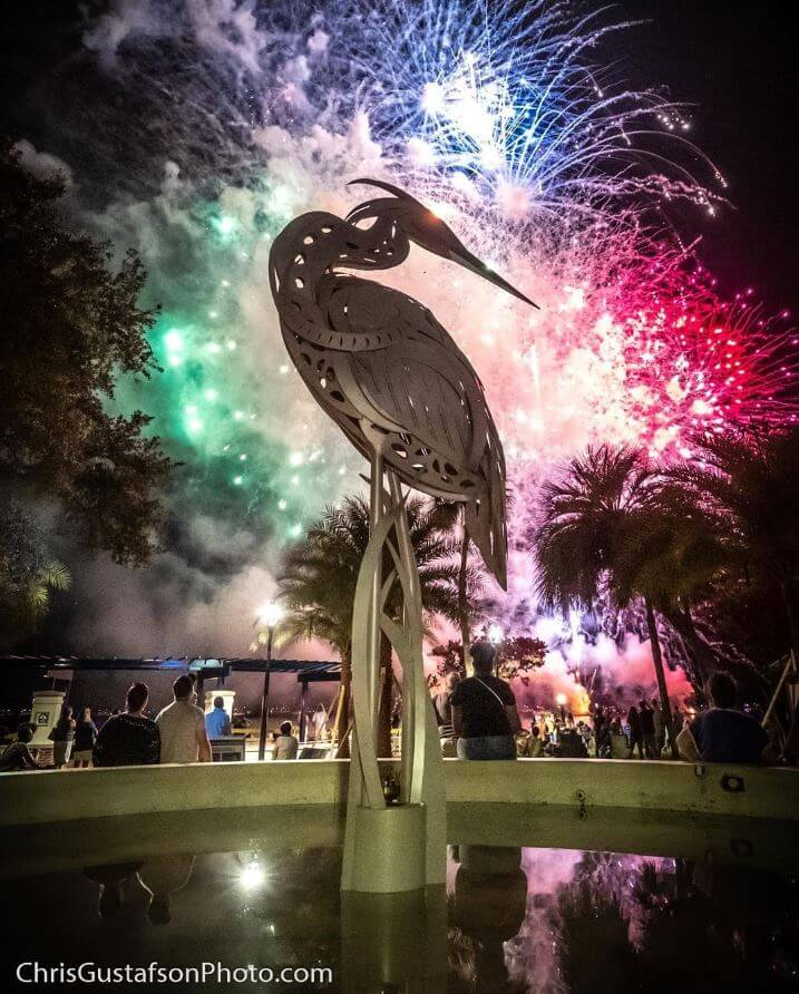 Photo of the crane statue at Ferran Park in Eustis. Fireworks are going off in the sky behind it.