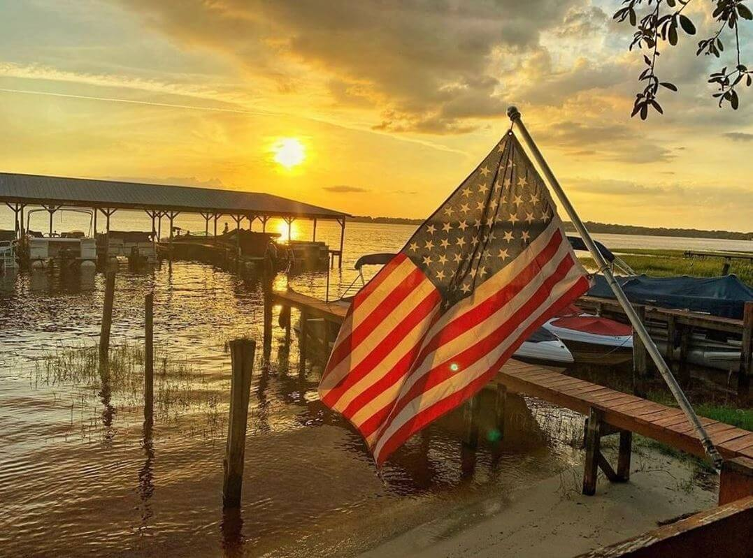 An American flag waves on the shores of Lake Minneola at sunset. Boats are docked in the distance.
