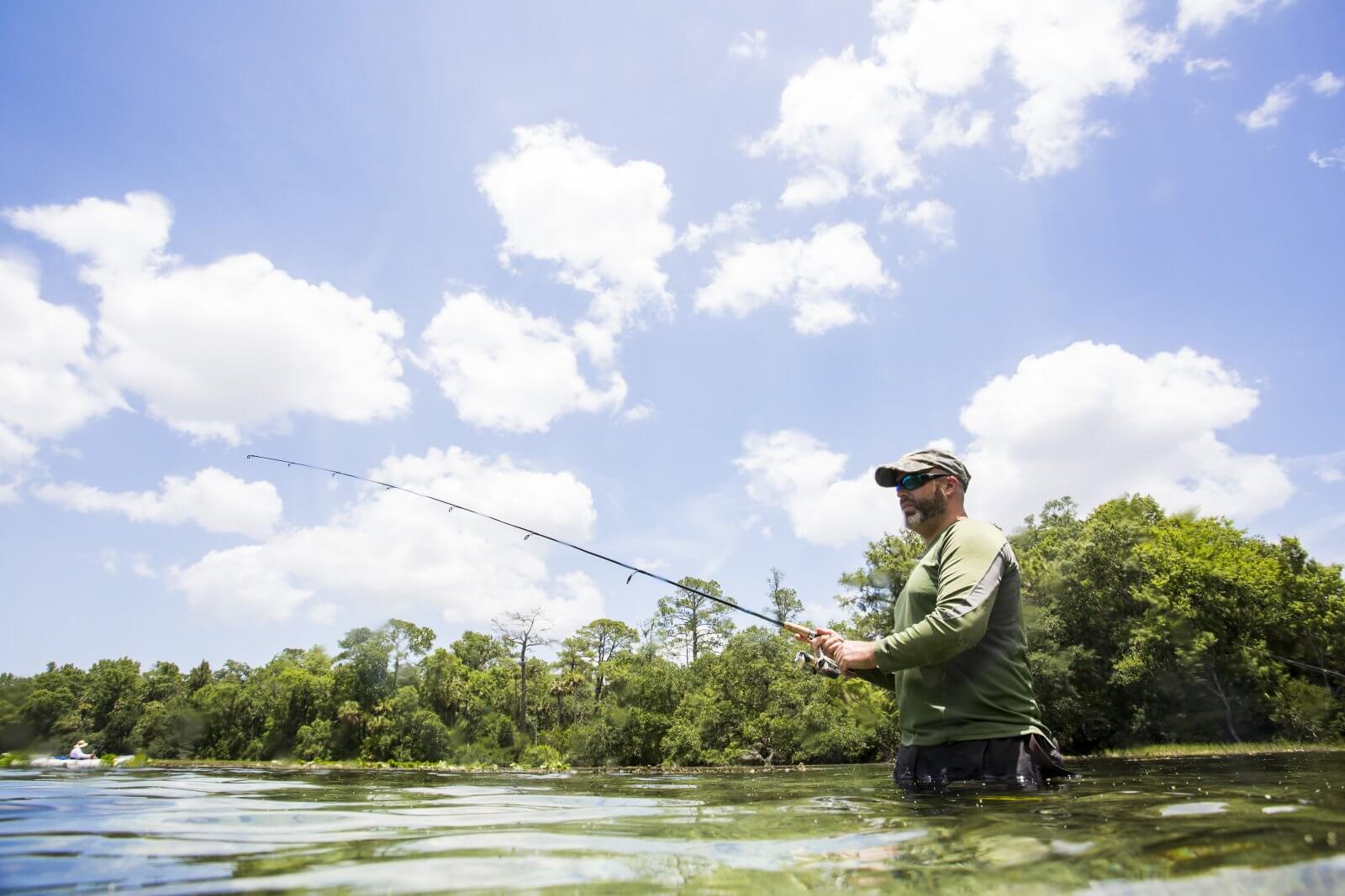 man standing in waste deep water fishing