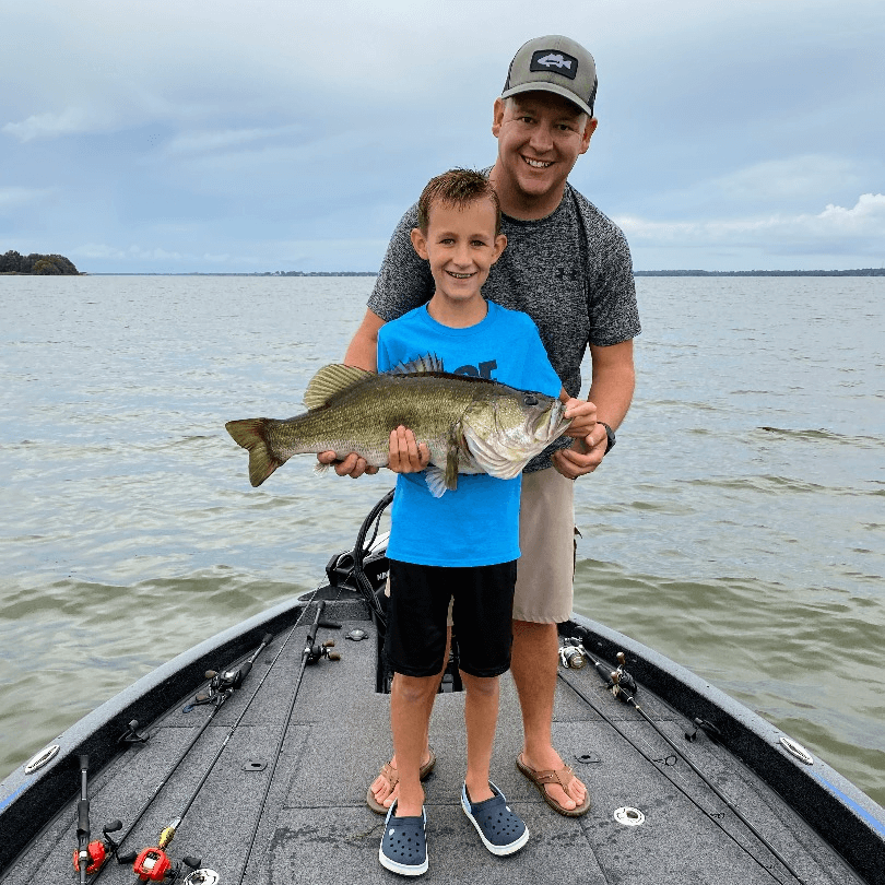 man and young boy smiling and displaying a largemouth bass they caught while standing on the deck of a bass boat in the middle of a lake.