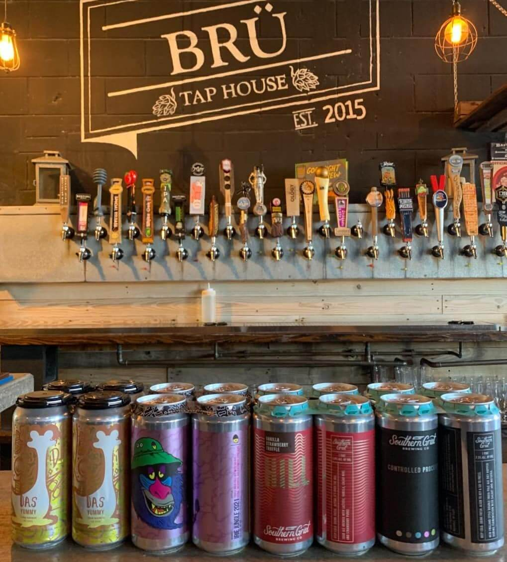 Photo inside Bru Tap House brewery showing beer cans and taps.
