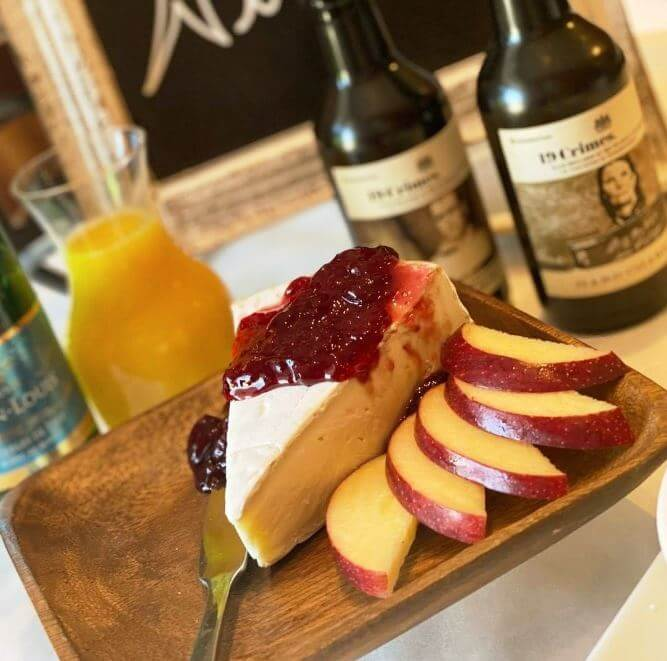 Photo of a cheese plate with cheese, sliced apple, jam and wine.